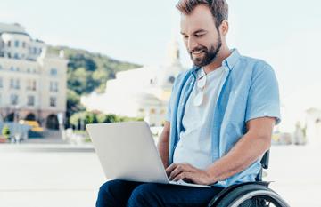 smiling man in wheelchair on laptop