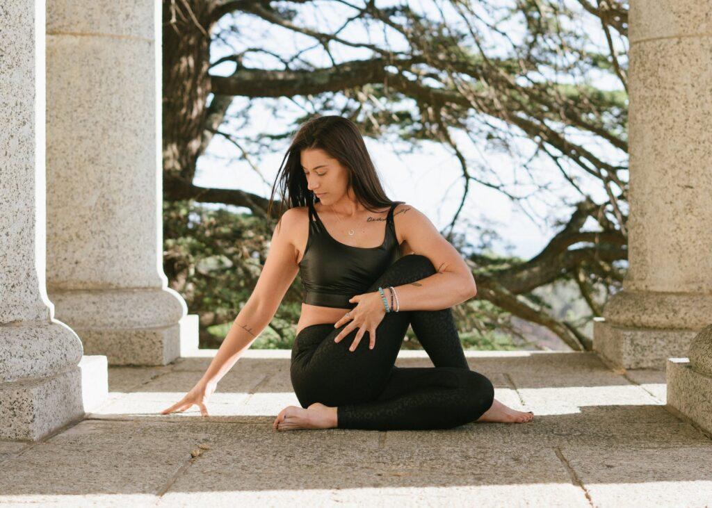 woman in black tank top and black leggings sitting on floor