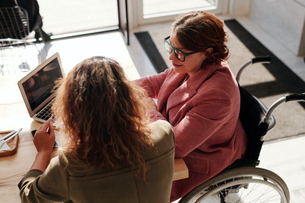 woman in red sweater wearing black framed eyeglasses sitting on wheelchair